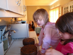 Girls take paper off christmas cakes